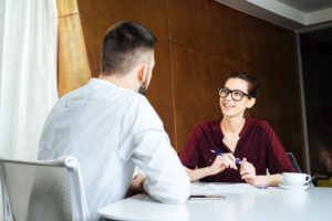 Smiling beautiful businesswoman in glasses talking to young businessman in meeting room